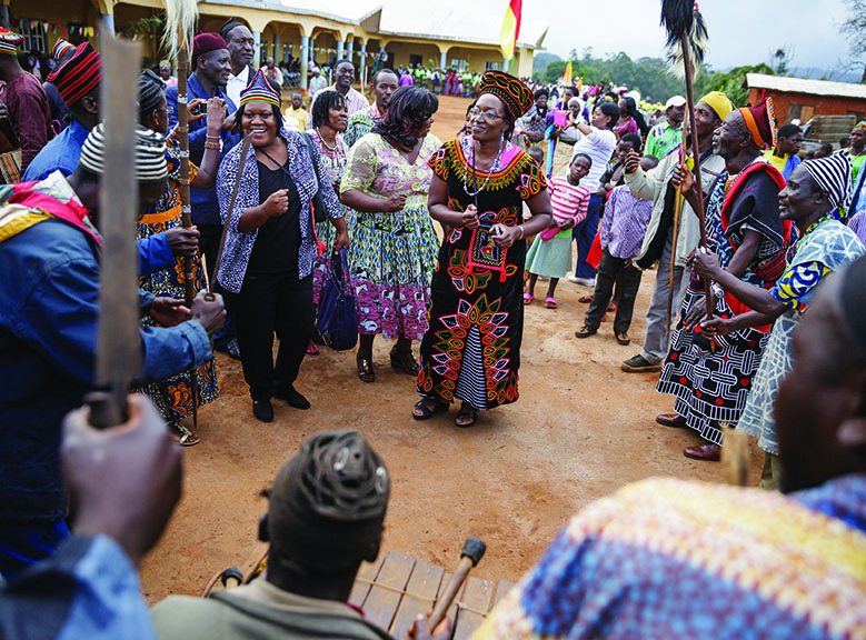 Heifer Africa Area Program Vice President Elizabeth Bintliff (center) dances with Heifer staff and traditional dancers outside the Fon of Nseh's palace.