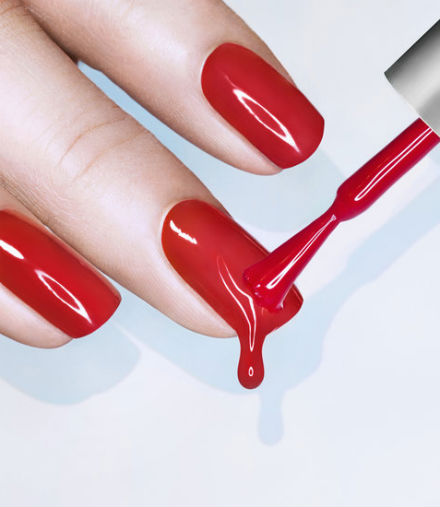 An image of a woman's fingers being painted red.