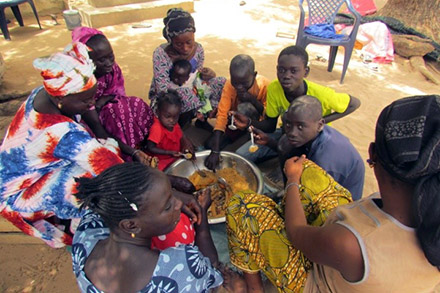 Gagnessiri's family sits down together to eat lunch.