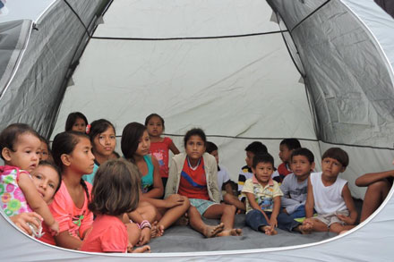 children taking refuge in a tent